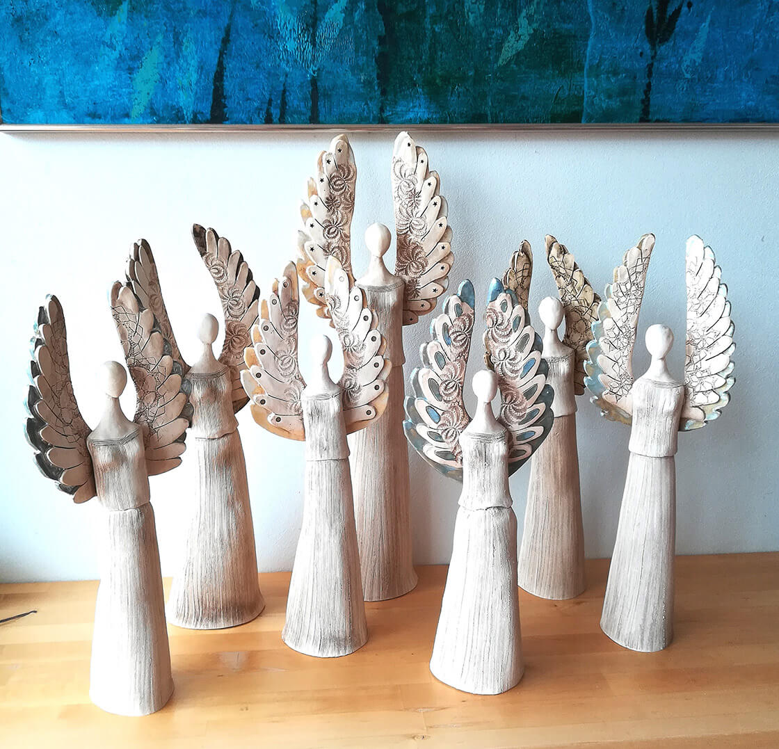 Skupina různě velkých keramických andělů s velkými křídly z ateliéru Vlaďky Zborníkové