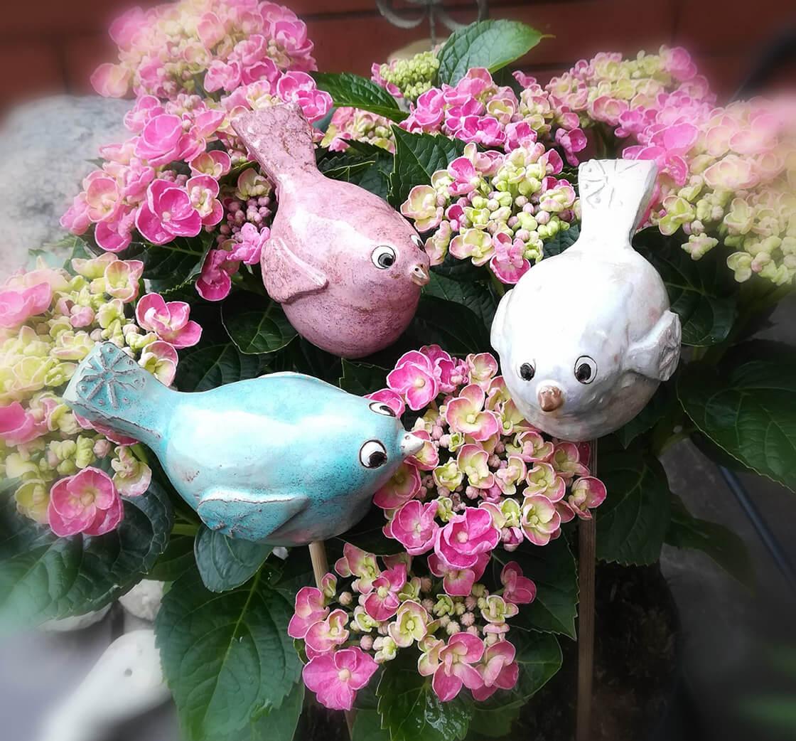 tři keramičtí ptáčci různých barev, zápich v květech hortenzie